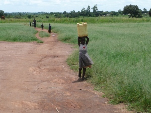 "A daily chore. She is carrying the standard 5 gallon ""jerry can"" of water to her home."